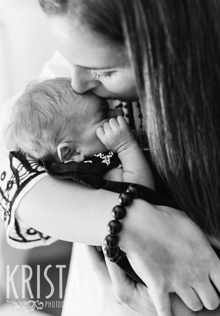 black and white image of mother and newborn baby girl snuggling during lifestyle family newborn baby portrait session