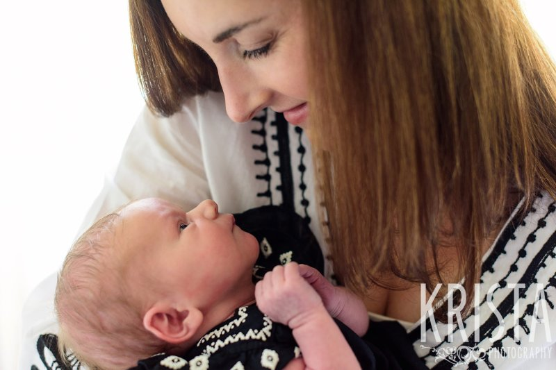 mother looking at newborn baby girl during lifestyle family portrait session in family home