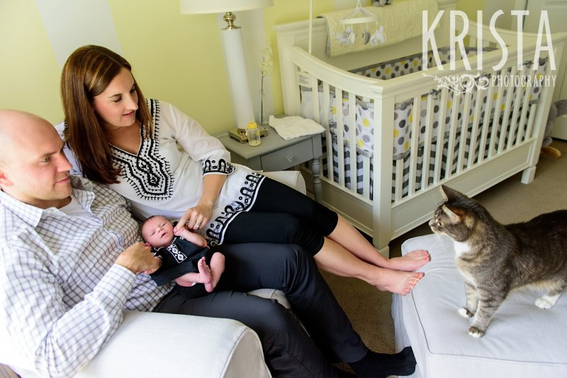 family sitting on nursing glider in yellow white and gray nursery with newborn baby girl and cat during lifestyle family portrait session at their home