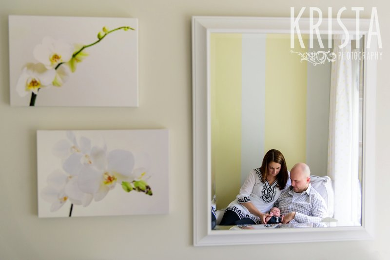 mother, father and newborn baby girl reflected in mirror of yellow, white and gray nursery during lifestyle family portrait session at family home