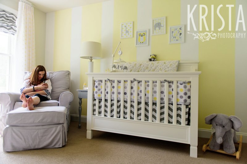 mother nursing newborn baby girl on white arm chair in yellow white and gray nursery during lifestyle family portrait session at family home