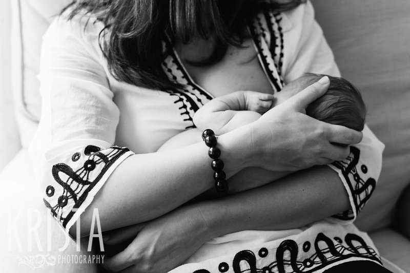 black and white image of mother nursing newborn baby girl during lifestyle family portrait session at home