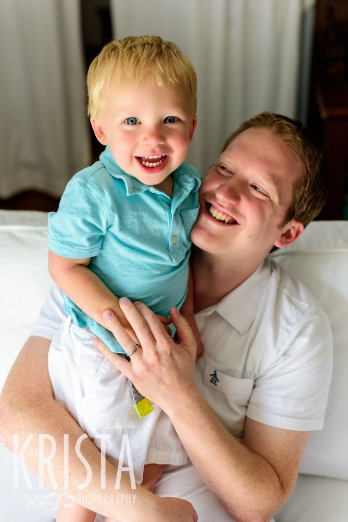 father and toddler son laughing in blue and white during lifestyle family portrait session at home