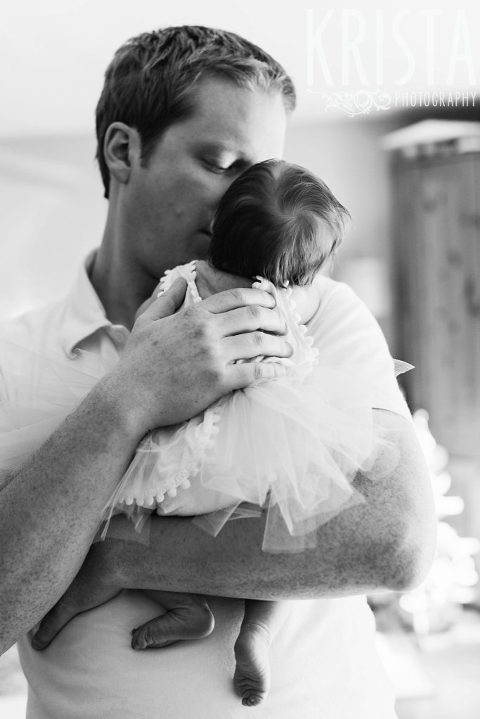 black and white of father holding newborn baby girl in arms during lifestyle family portrait session