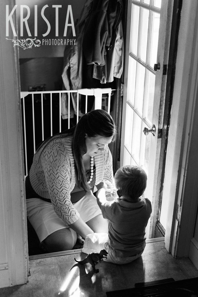 black and white image of mother helping toddler son put on shoes to go outside during lifestyle family portrait session