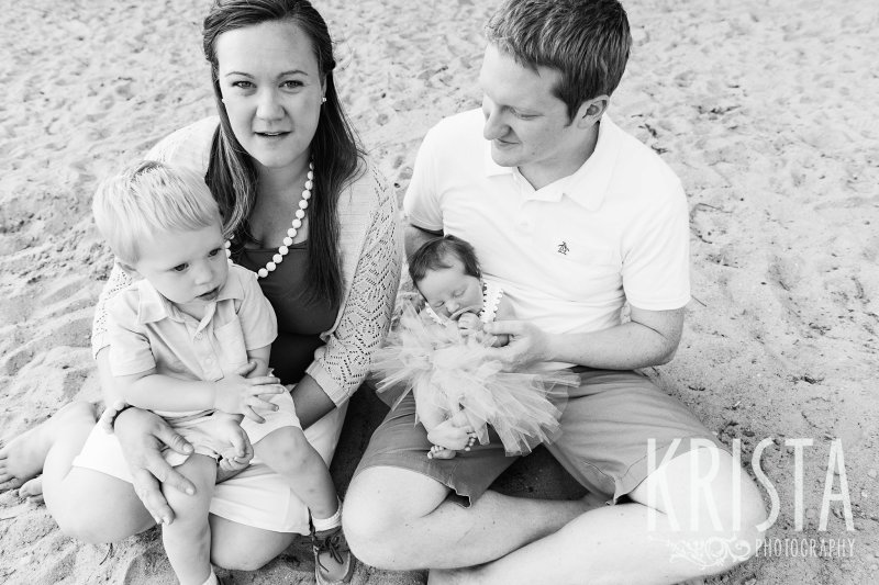 black and white of family in backyard during lifestyle family session with toddler boy and newborn baby girl