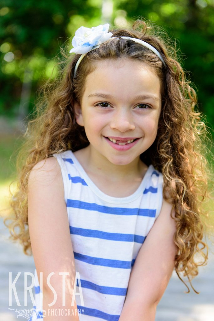 little curly haired girl in blue and white stripes sitting among green trees during springtime mini portrait sessions in New England