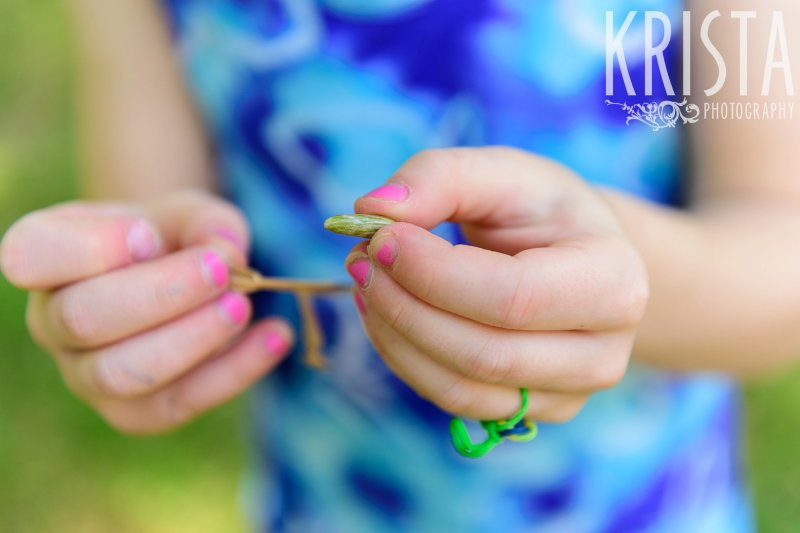 two sisters concentrating on making flower jewelry during springtime mini portrait sessions in New England