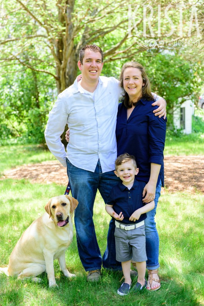 little boy in navy blue collared shirt with his golden retriever and parents among green trees during springtime mini portrait sessions in New England