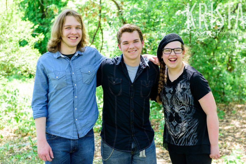 two brothers with their sister who is wearing a black beanie cap and black framed glasses among green trees during mini portrait sessions in New England