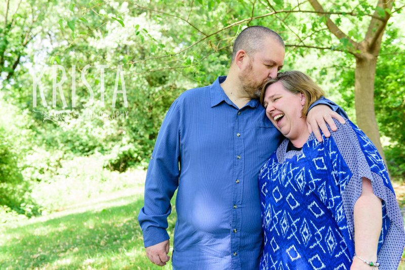 husband kissing wife on top of head as she laughs with mouth open among green trees during mini portrait sessions in New England