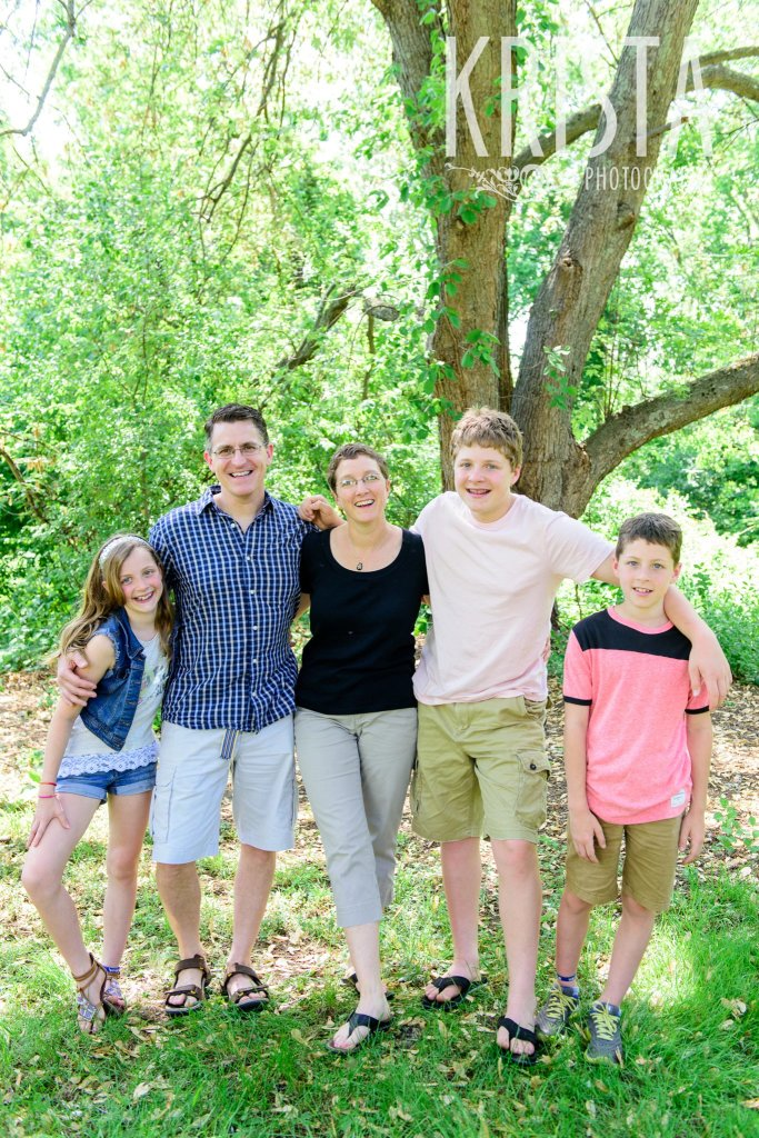 family of five with arms around one another among green trees during springtime mini portrait session in New England