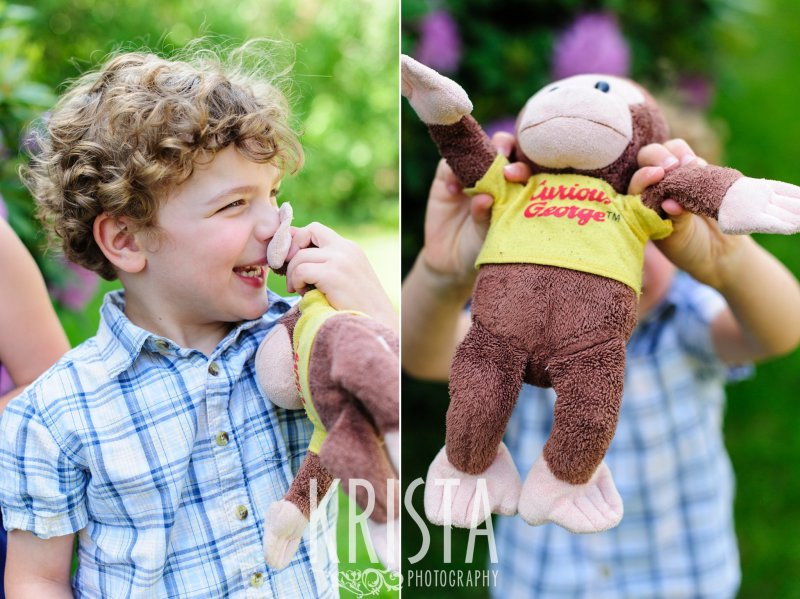 little boy with his curious george stuffed animal among green trees during springtime mini portrait sessions in New England