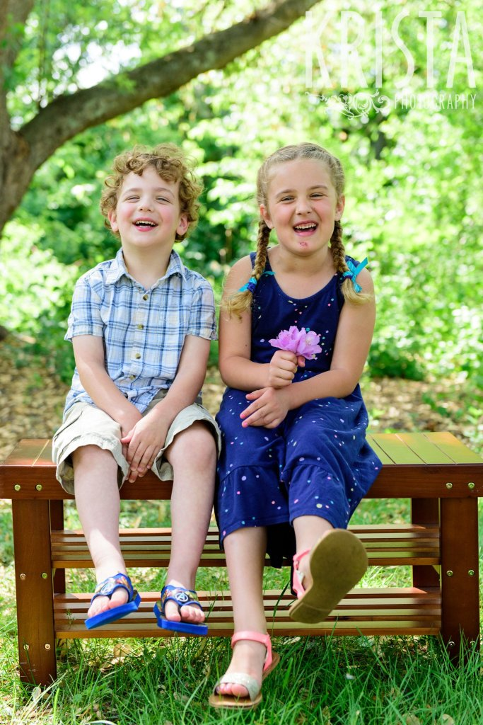 young brother and sister sitting on wooden bench laughing among green trees during springtime mini portrait session in New England