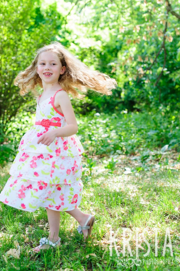 twirling little girl in floral dress among green trees during spring mini portrait session