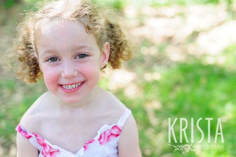 adorable little girl with curly hair in two pigtails in floral dress among green grass during spring mini portrait session