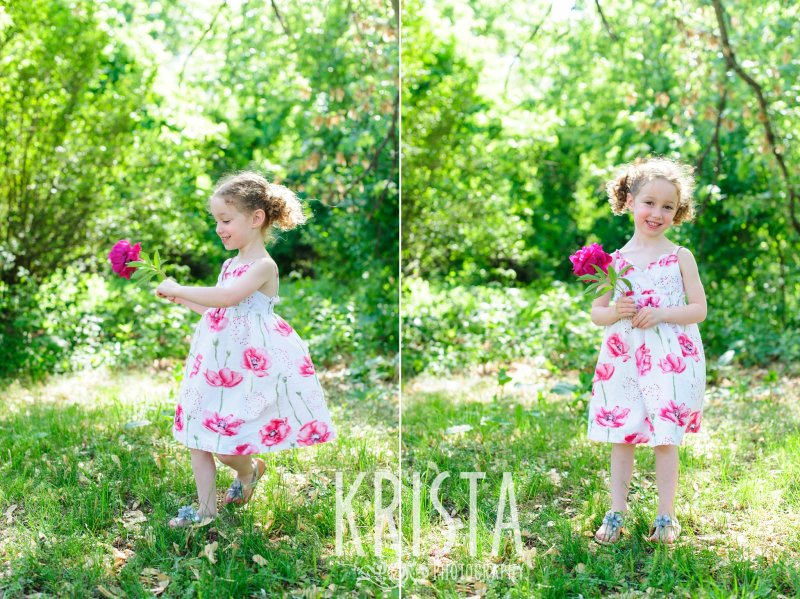 sweet little girl with curly pigtails twirling in grass with pink flowers during spring mini portrait session