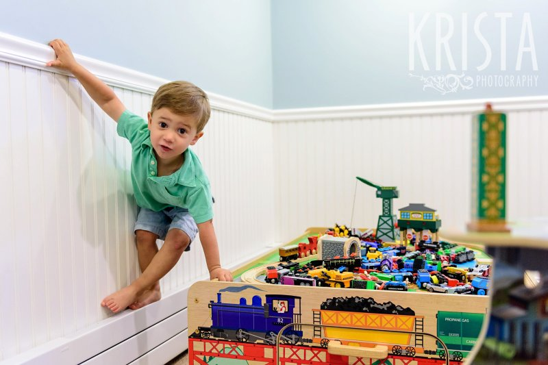 young boy in green collared shirt walking along baseboards of house while playing with train table