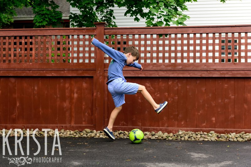 boy kicking soccer ball on driveway during lifestyle family portrait session at home