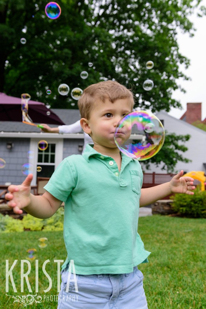 brothers playing with bubbles in backyard during lifestyle portrait session at home