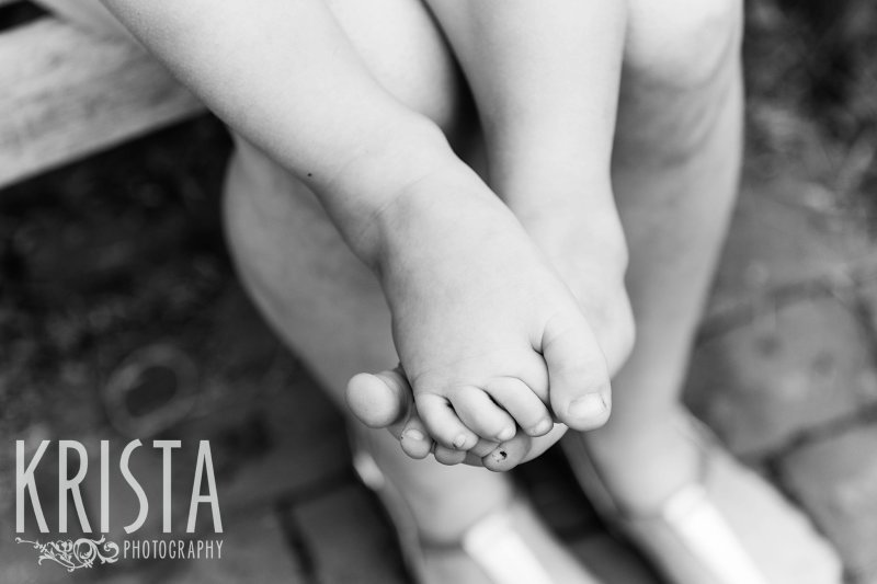black and white of little boys feet while sitting on mother's lap