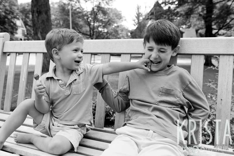 black and white brothers sitting side by side on outdoor bench younger boy punching at older boy who is laughing