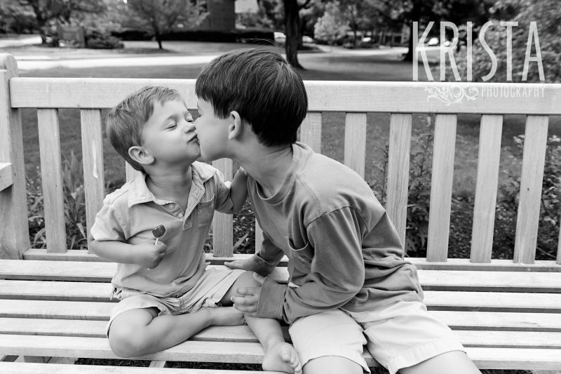 black and white brothers kissing on outdoor bench