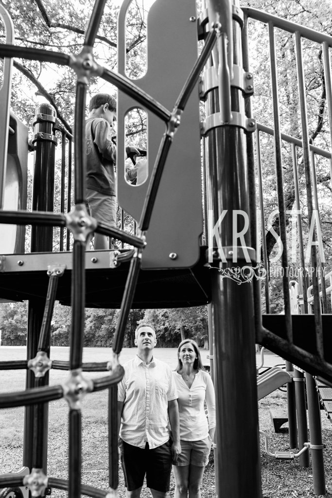 black and white of parents watching kids from below playing on structure at playground