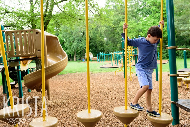 young boy in blue crossing a play structure on playground