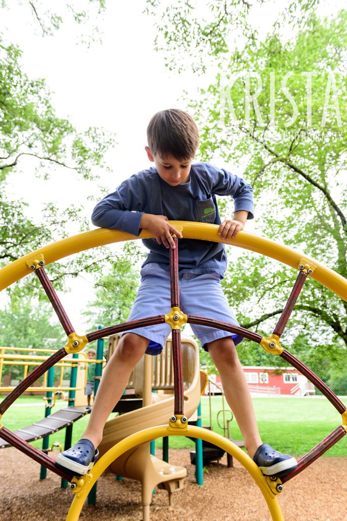 young boy in blue climbing structure on playground