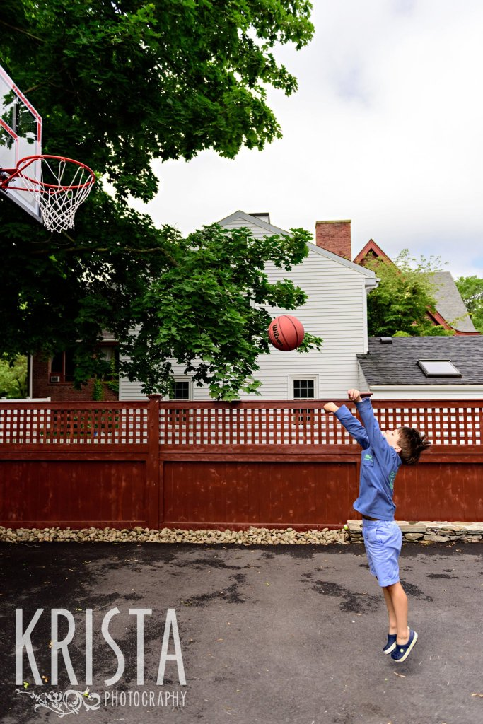 young boy in blue shooting basketball at hoop on driveway of home