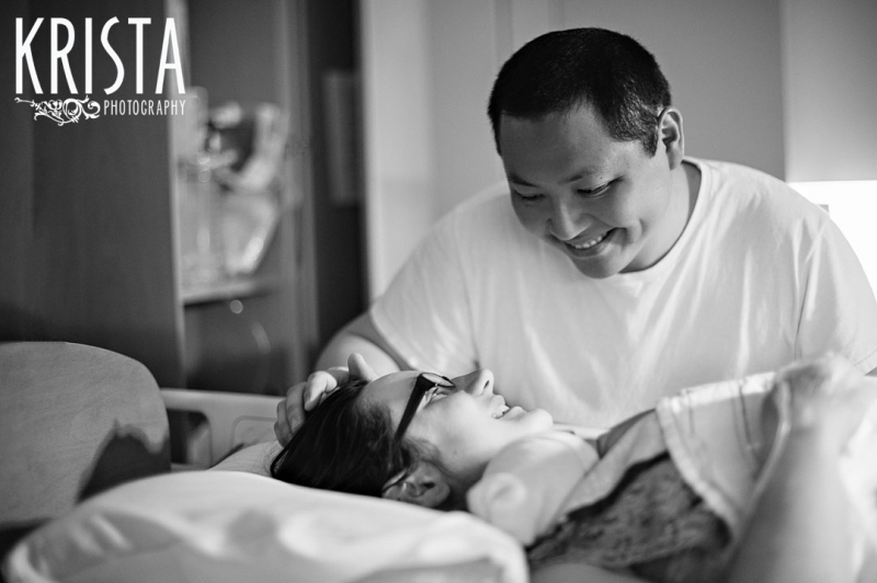 black and white image of father looking down at new mother holding newborn baby boy in hospital during lifestyle portrait session