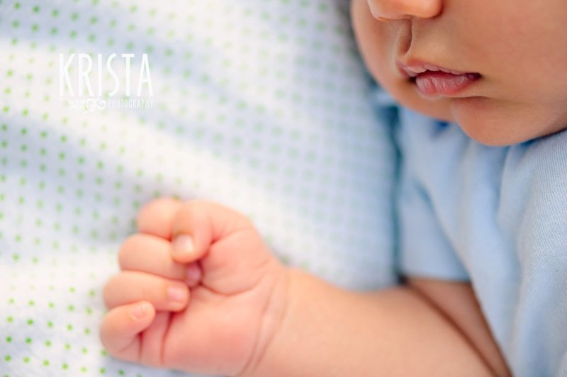newborn baby boy at one month old during lifestyle portrait session with family outside