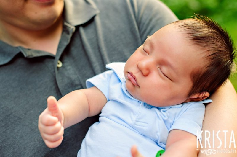 newborn baby boy giving thumbs up while sleeping during outdoor lifestyle portrait session at family's home
