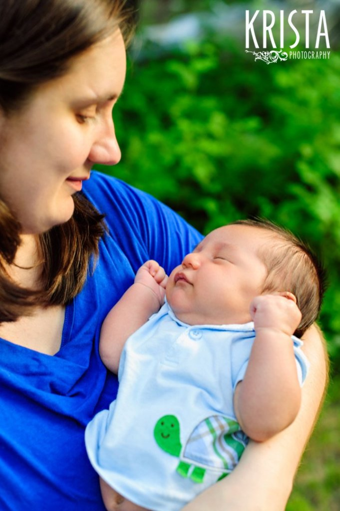 new mother gazing adoringly down at newborn baby son during outdoor lifestyle portrait session at family's home