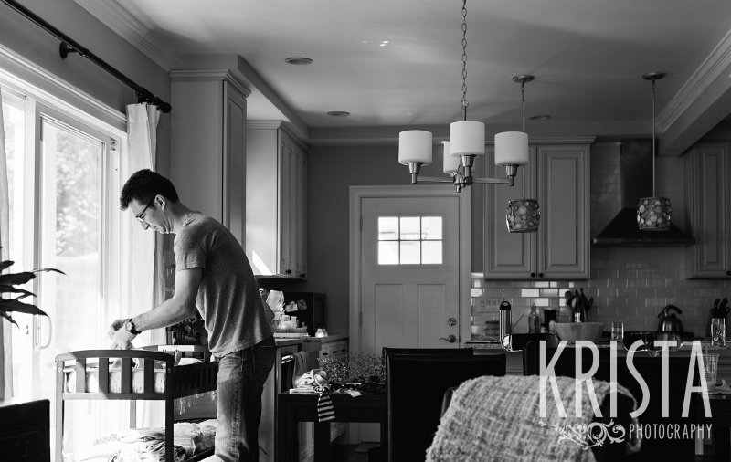 black and white of father changing newborn baby diaper at home