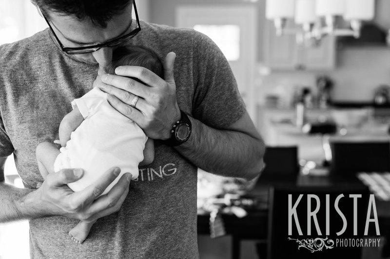 black and white image of father kissing newborn baby on head at home