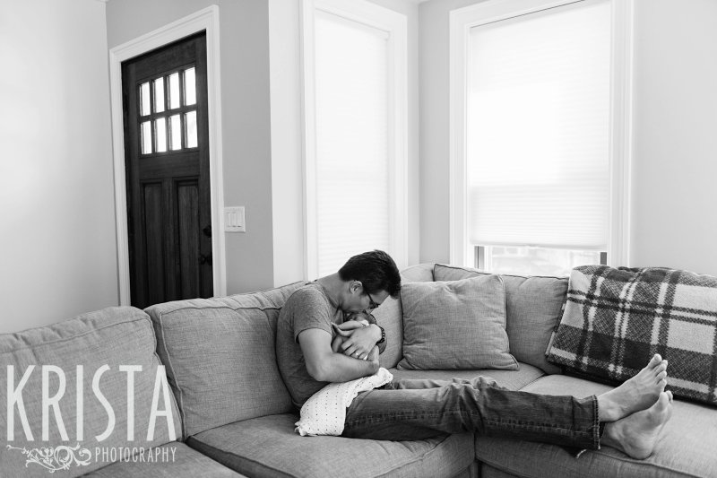 black and white of father cuddling newborn baby twin in home during portrait session