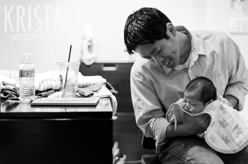 black and white image of father burping newborn baby boy during family portrait session in their home
