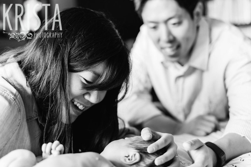 black and white image of parents cooing at newborn baby boy