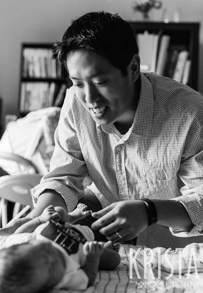 black and white image of father trying to cheer up newborn baby boy during portrait session at family home