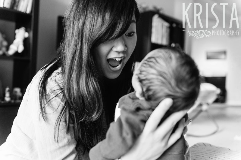 black and white image of mother trying to cheer up newborn baby boy during portrait session at family home