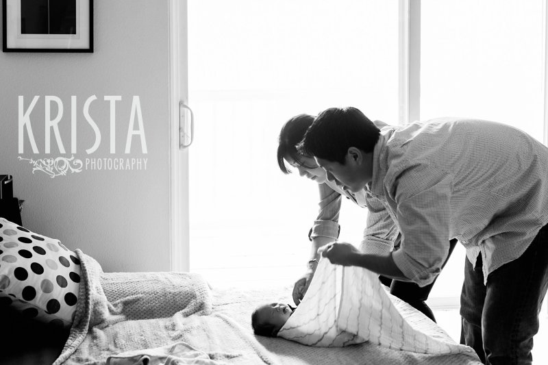 black and white image of parents swaddling newborn baby boy during portrait session at family's home