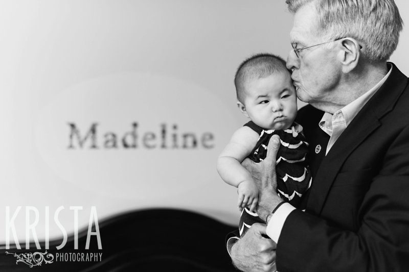 black and white image of baby girl in grandfather's arms unhappy to be woken up from nap for lifestyle portrait session at home