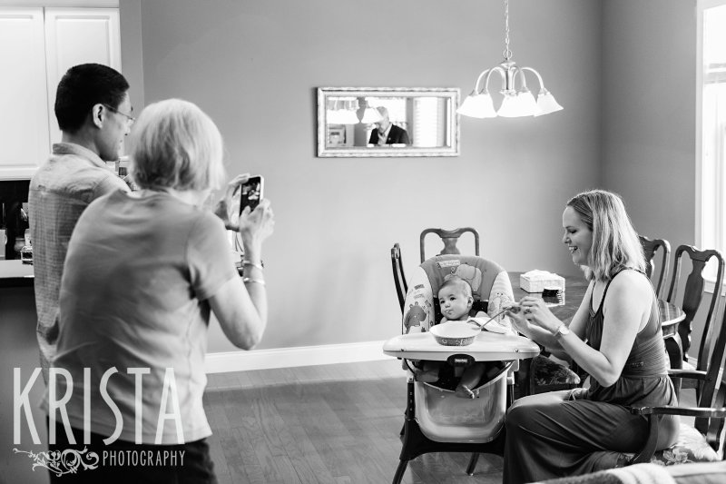 black and white image of baby trying first spoonfuls of cereal from parents and grandparents during lifestyle portrait session at home