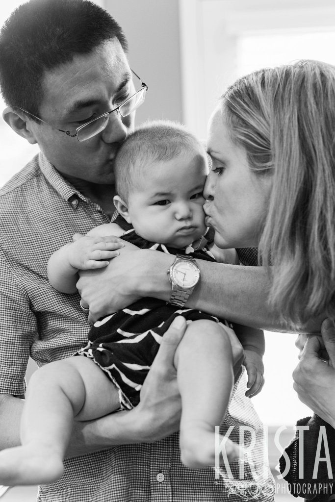 black and white image of new parents kissing baby girl who is not happy to be awake on the cheek during lifestyle portrait session at home