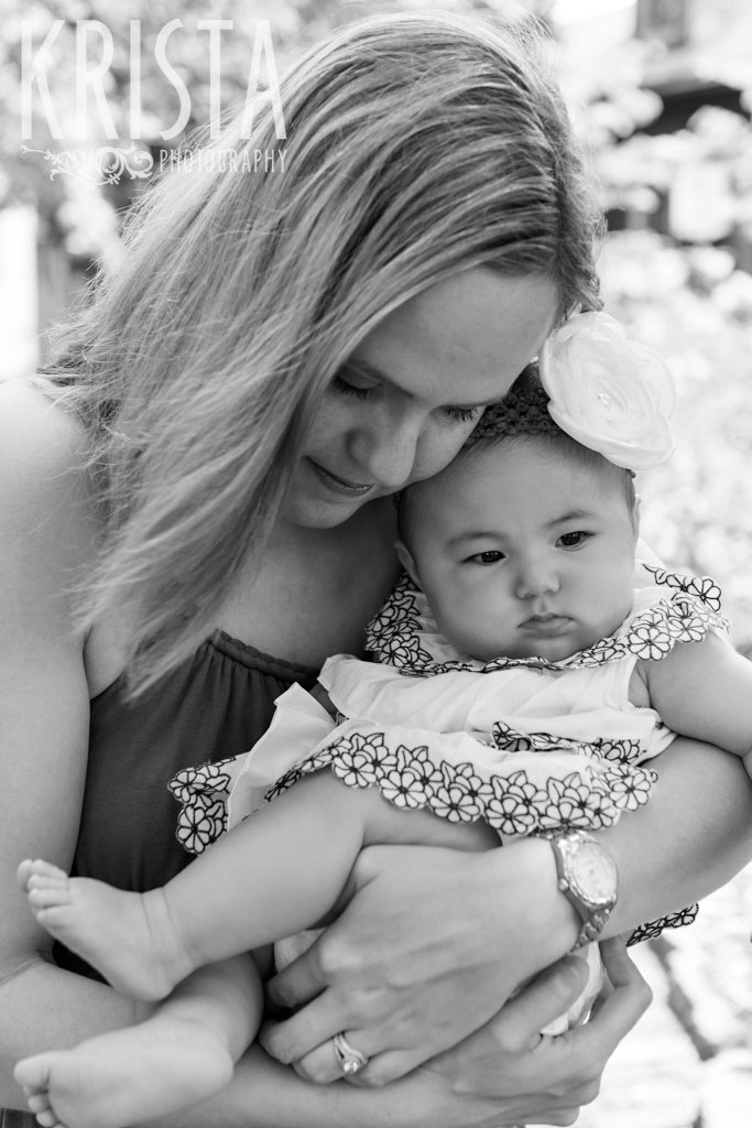 black and white image of mother with baby girl snuggling outside of home during lifestyle portrait session at home