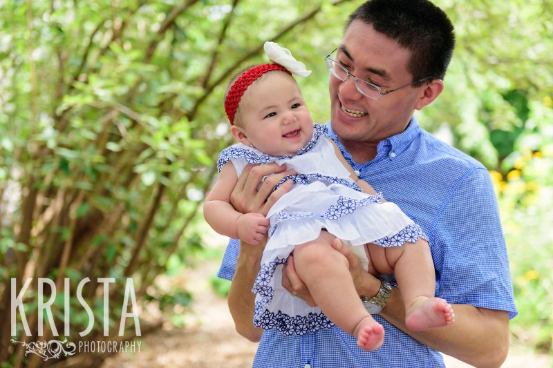 baby girl in father's arms among trees in their yard during lifestyle portrait session
