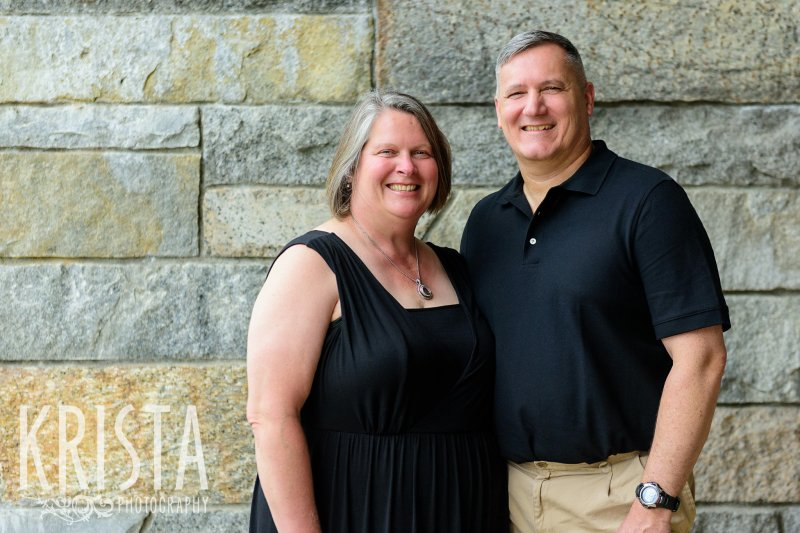 parents beside stone wall during family portrait session in winchester, ma