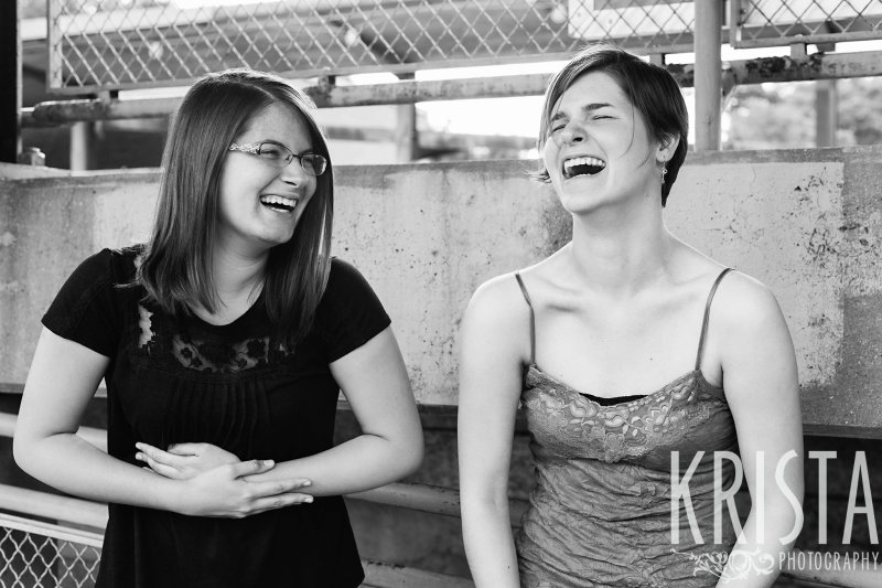 black and white image of sisters laughing during lifestyle portrait session near family's home